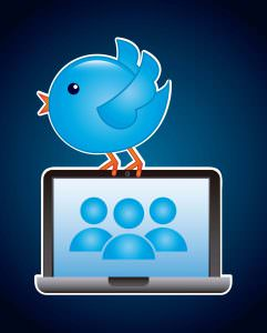 This is a picture of the Twitter bird sitting on top of a laptop.