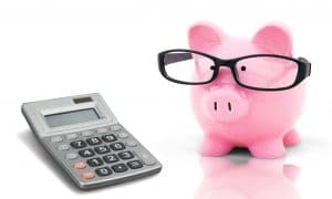 Piggy bank wearing glasses, standing next to a calculator