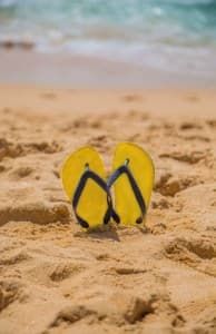 This is a picture of flip flops on a beach.