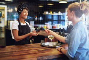 Customer in a pub paying the business owner or waitress with a credit card to be processed on a handheld banking machine, focus to the attractive african american owner