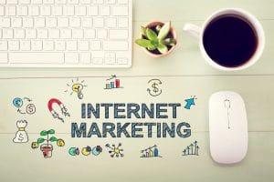 Internet marketing concept with workstation on a light green wooden desk