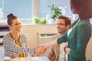Business people shaking hands at desk and smiling in the office