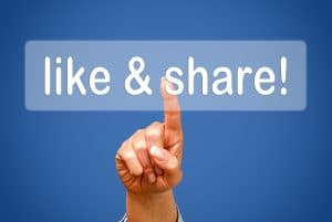 Hand clicking on a sign that says Like & Share