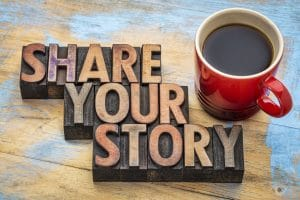Share your story word abstract - inspirational text in vintage letterpress wood type with a cup of coffee.