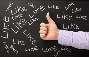 Social media concept with a male hand giving a thumbs gesture on a blackboard where the word like has been written several times in white chalk