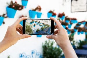 Female hands taking a picture with mobile phone in a white villa