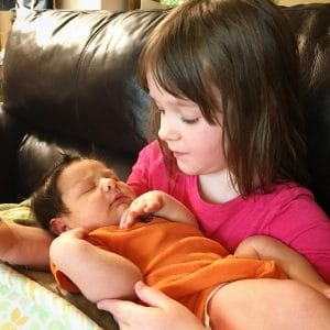 A picture of a little girl holding her baby brother.