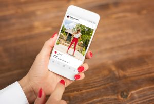 Woman looking through an instagram post based on a popular hashtag, it is a woman in red pants on instagram