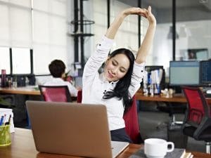 Businesswoman looking at work on laptop computer with satisfaction and stretching arms in the air.