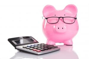 A piggy bank wearing glasses next to a calculator to symbolize marketing budget