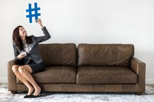 Businesswoman sitting on couch holding hashtag icon