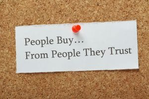 "A note pinned on a cork board that says ""People Buy...From People They Trust."""