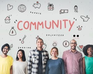 A group of people standing in front of a sign that says community with symbols around it.