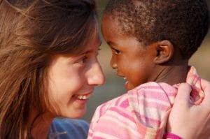 A woman doctor holding an African childn.