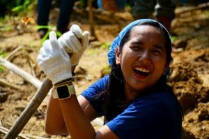 A smiling young girl volunteering.