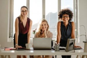 Portrait of three smiling young businesswoman standing at desk and smiling at camera.