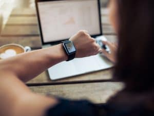 Close up shot of a woman checking time on her smartwatch. Female sitting in cafe with a laptop and cup of coffee.