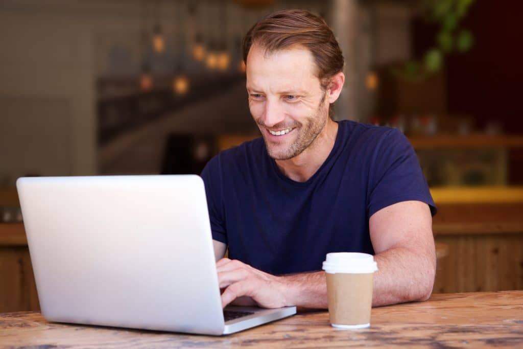 Man smiling at his laptop as he receives a relational email.