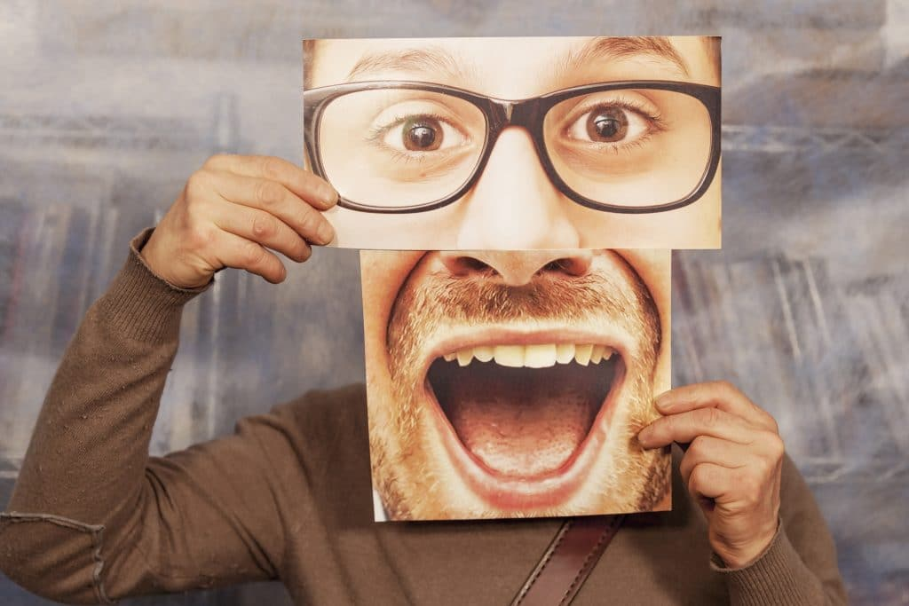 man holding a card with a big smile and big glasses on it
