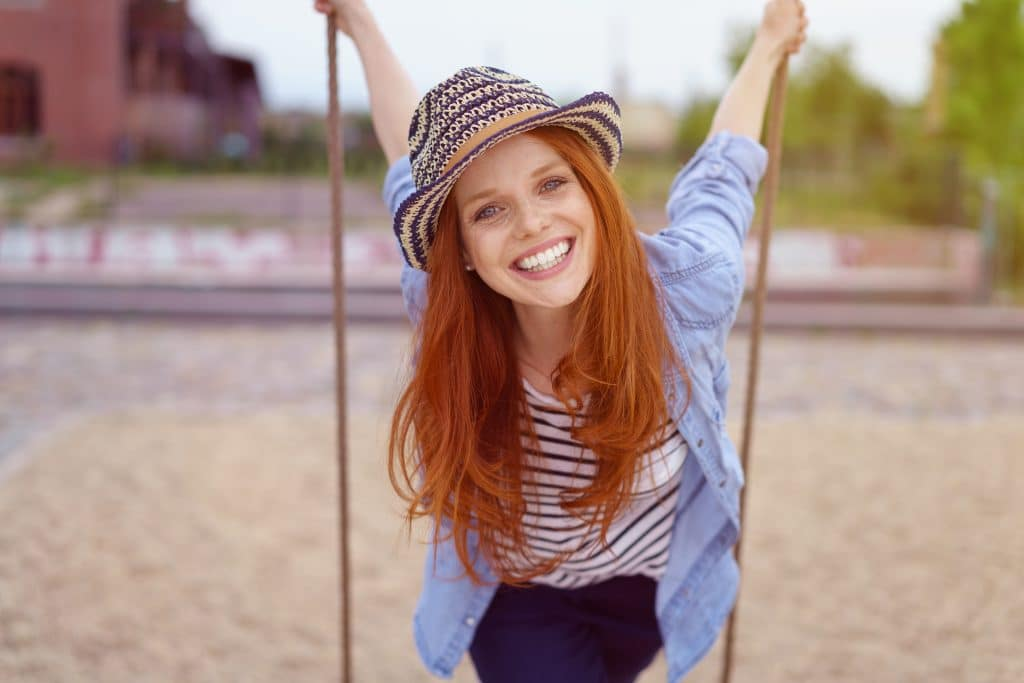 Vivacious pretty young redhead woman in a trendy outfit with a hat leaning forward on a swing in an urban park