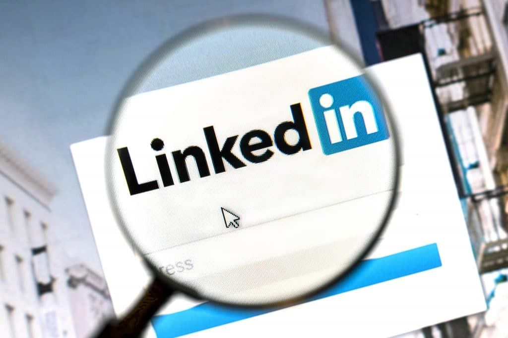 Magnifying glass over LinkedIn logo.