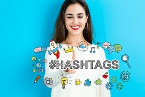 A smiling woman standing in front of a cloud with hashtags.