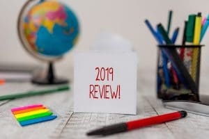 Text sign showing 2019 Review. Business photo text remembering past year events main actions or good shows Stationary and paper sheets plus small arrows with globe on the wooden desk