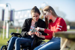 Two teenage girls looking down at phones and smiling.