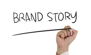 A hand writing the word brand story.