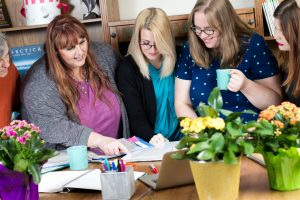 Three Girls Media's team of content marketers looking at documents together