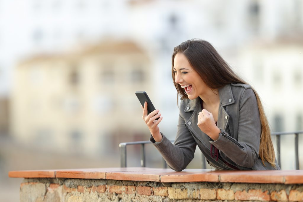 Woman is excited looking at iPhone while outdoors. This is to show that people will be excited to find what they are looking for on search engines if your business shows up first on Google.