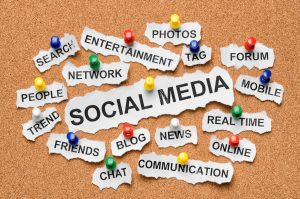 """The word """"social media"""" is pinned to a corkboard. Words having to do with social media, like """"Communication"""", """"Chat"""", """"Mobile"""", etc are pinned to the corkboard surrounding it."""