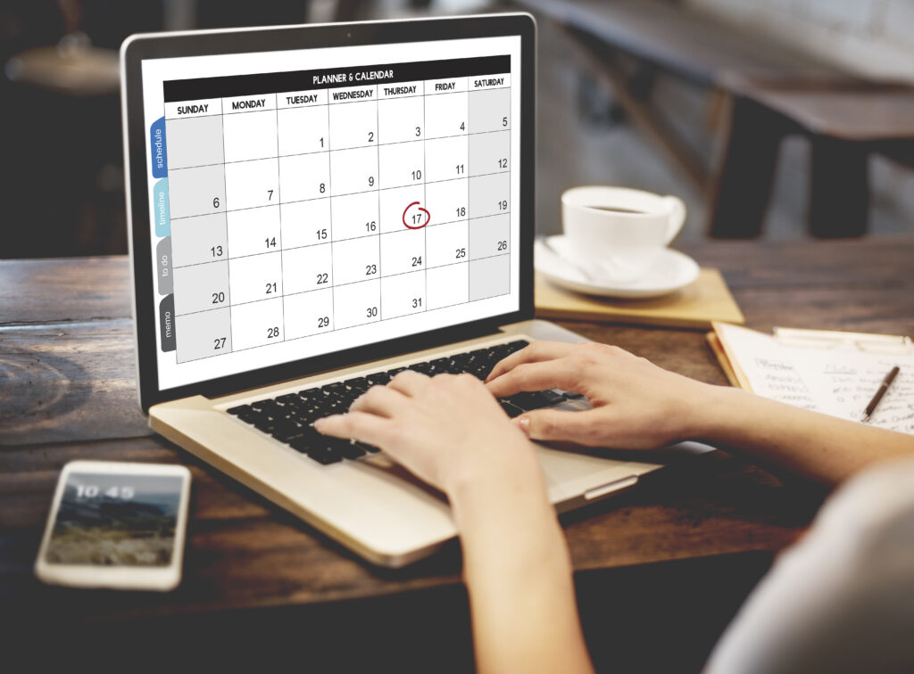 Person typing on laptop and scheduling on a calendar