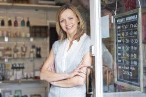 Small business owner standing in shop doorway