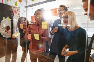 Diverse group of coworkers working together to simplify workflow with sticky notes