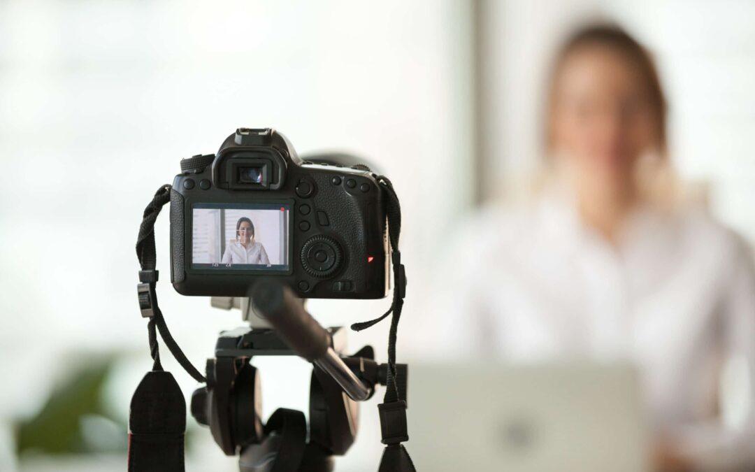 a photo of a camera on a tripod filming a woman