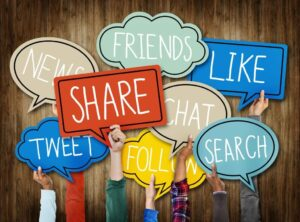 """Hands holding up signs that say """"share"""", """"search"""", """"tweet"""", and other social media terms"""