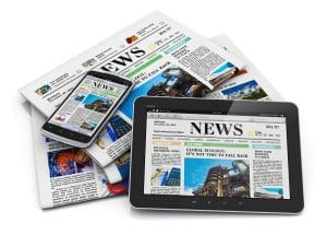 A stack of newspapers, with a smartphone and tablet on top showing the news as well. Press strategy