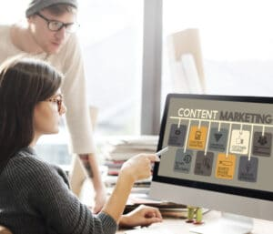 """Two people look at computer screen with the words """"content marketing"""" on it."""