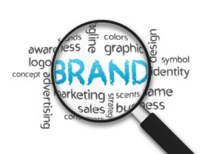 A microscope hovers over the word BRAND, with smaller words such as graphic, color, sales and marketing surround it.