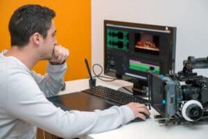 A man sits at his computer looking at video editing software
